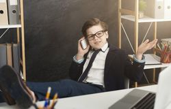 Relaxed business boy talking on mobile phone. Sitting with legs on table on office, copy space royalty free stock photo