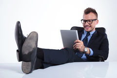 Relaxed business man reads on tablet Stock Photo