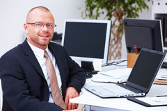 Relaxed business man sitting with laptop in office Stock Image