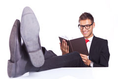 Relaxed business reading a book. With his feet on the desk top Stock Photos