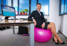 Relaxed business woman. Sitting on pink pilates ball in the office Stock Photos