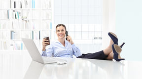 Relaxed business woman drinking coffee and talking on the phone Royalty Free Stock Photo