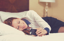 Relaxed business woman reading a text message in her bedroom or hotel room after work Stock Image
