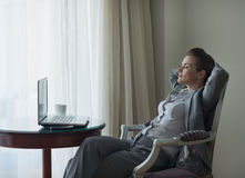 Relaxed business woman sitting in chair in room Royalty Free Stock Photo