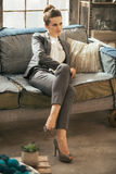Relaxed business woman sitting on sofa in loft Stock Images