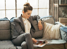 Relaxed business woman sitting on sofa in loft Royalty Free Stock Image