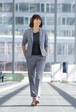 Relaxed business woman smiling and walking royalty free stock photo