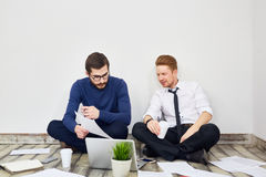 Relaxed Business Work. Portrait of two business people sitting cross legged on floor in office, talking,  using laptop and working with documentation laid out Royalty Free Stock Images