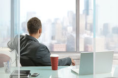 Relaxed businessman. Sitting at desk in office, looking out the windows to downtown skyscrapers Royalty Free Stock Photography