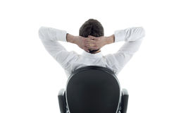 Relaxed Businessman. Rear viwe of a relaxed businessman with hands behind his head Stock Image