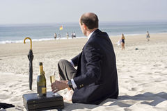 Relaxed businessman. A back view of a businessman sitting on the beach in a suit. He has his briefcase, umbrella and a bottle of wine with him Royalty Free Stock Photo