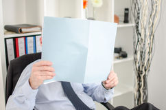 Relaxed businessman analyzing a document Royalty Free Stock Images