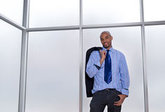 Relaxed businessman beside a big office window. Good-looking relaxed businessman standing beside a big office window Royalty Free Stock Photo