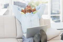 Relaxed businessman on the couch with laptop Royalty Free Stock Images