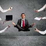 Relaxed businessman that does yoga during the work Stock Photos