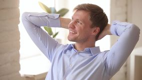 Relaxed businessman holding hands behind head enjoying business success. Relaxed businessman with happy face holding hands behind head enjoying business success stock video footage