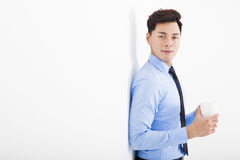 Relaxed businessman leaning against white wall in office Stock Images