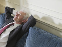 Relaxed Businessman Leaning Back On Sofa Stock Photo