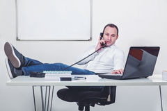Relaxed businessman with legs on the table talking on the phone. Relaxed businessman in his office with legs on the table talking and looking at computer Stock Photography