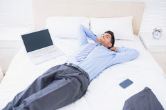 Relaxed businessman lying on his bed Royalty Free Stock Images