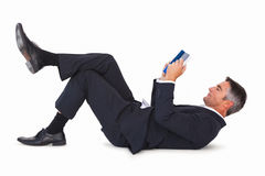 Relaxed businessman lying and reading book Stock Images