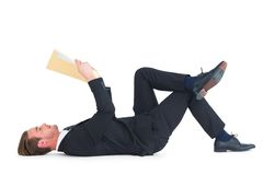 Relaxed businessman lying and reading document Stock Photos