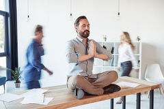 Relaxed businessman meditating in lotus position while coworkers moving. In office Stock Photos