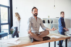 Relaxed businessman meditating in lotus position while coworkers moving. In office Royalty Free Stock Photo