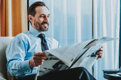 Relaxed businessman reading the newspaper and smiling stock photos
