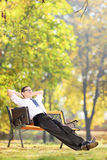 Relaxed businessman sitting on a bench in park Stock Photography