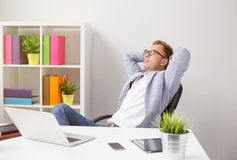Relaxed businessman sitting in chair with hands behind head Royalty Free Stock Photo