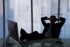 Relaxed Businessman Sitting At Computer Desk In Office Stock Photography