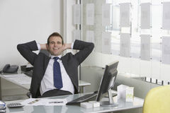 Relaxed Businessman Sitting At Desk In Office Royalty Free Stock Photos