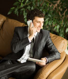 Relaxed businessman sitting in front of the Windows of the offic Royalty Free Stock Image
