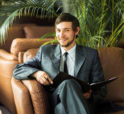Relaxed businessman sitting in front of the Windows Royalty Free Stock Photography