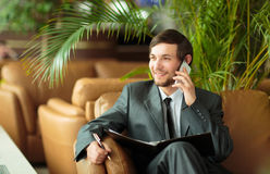 Relaxed businessman sitting in front of the Windows Royalty Free Stock Image