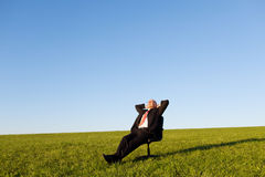 Relaxed Businessman Sitting On Green Grassland Royalty Free Stock Image