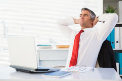 Relaxed businessman sitting and relaxing Royalty Free Stock Image