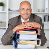 Relaxed businessman with a stack of binders Stock Images