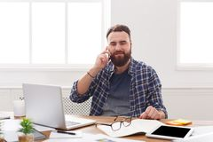 Relaxed businessman talk mobile in office. Relaxed businessman in casual talk mobile in office. Young businessman in casual has phone talk in modern workplace Royalty Free Stock Photos