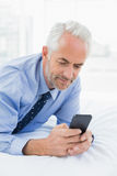 Relaxed businessman text messaging in bed Stock Photos
