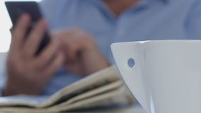 Relaxed businessman text using cellphone with newspaper and coffee on the table.  stock footage