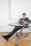 Relaxed Businessman Using Digital Tablet In Office Stock Photos