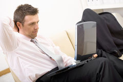 Relaxed businessman using laptop Stock Image