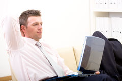 Relaxed businessman using laptop Royalty Free Stock Photography