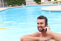 Relaxed businessman using phone by swimming pool.  Stock Photo