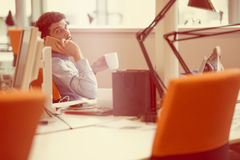 Relaxed businessman at workplace at early morning, relaxing, at startup office. Relaxed young businessman at workplace at early morning, relaxing, at modern Stock Photography