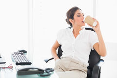 Relaxed businesswoman drinking a coffee at her desk Stock Photos