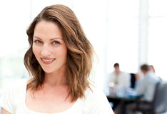 Relaxed businesswoman in front of her teamwork Stock Image