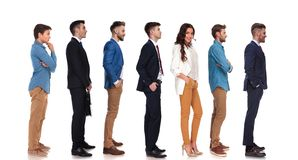 Relaxed businesswoman and group of men waiting in line. While standing on white background, full length picture stock photos